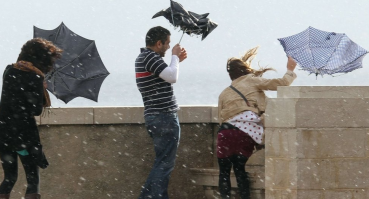 People-struggle-with-umbrellas-in-high-wind-speed