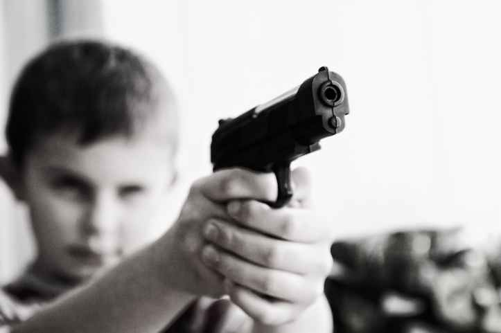 grayscale photo of a boy aiming toy gun selective focus photography